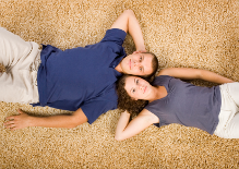 couple-relaxing-on-carpet